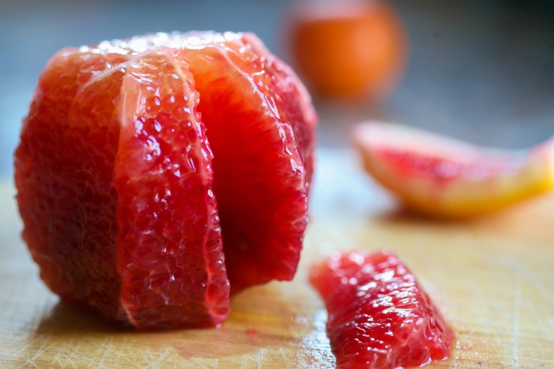 Blood orange with peel and pith removed, one segment cut out