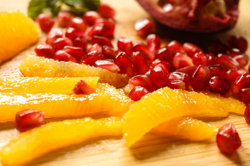 Orange segments and pomegranate seeds on a cutting board