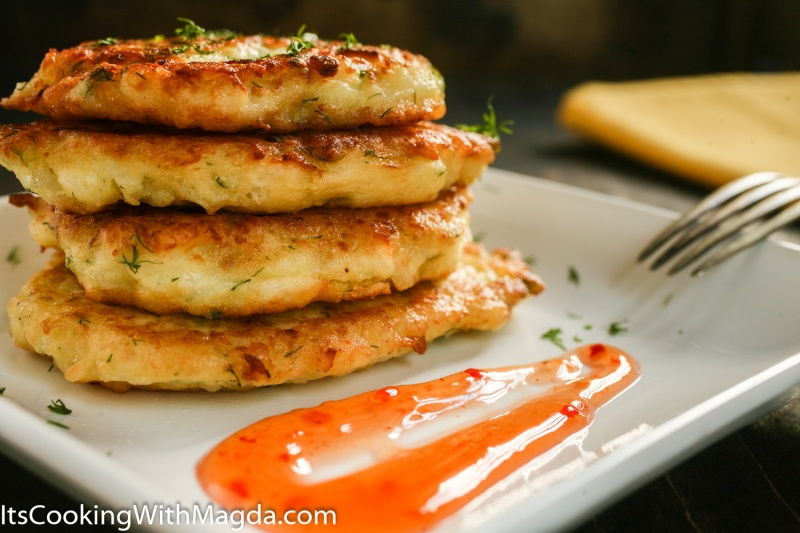 cauliflower fritters stacked on a white plate with sweet sauce