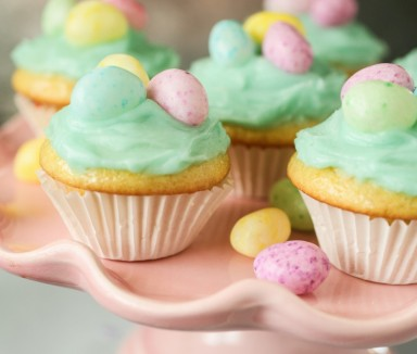 lemon cupcakes with jelly beans on a pink cake stand