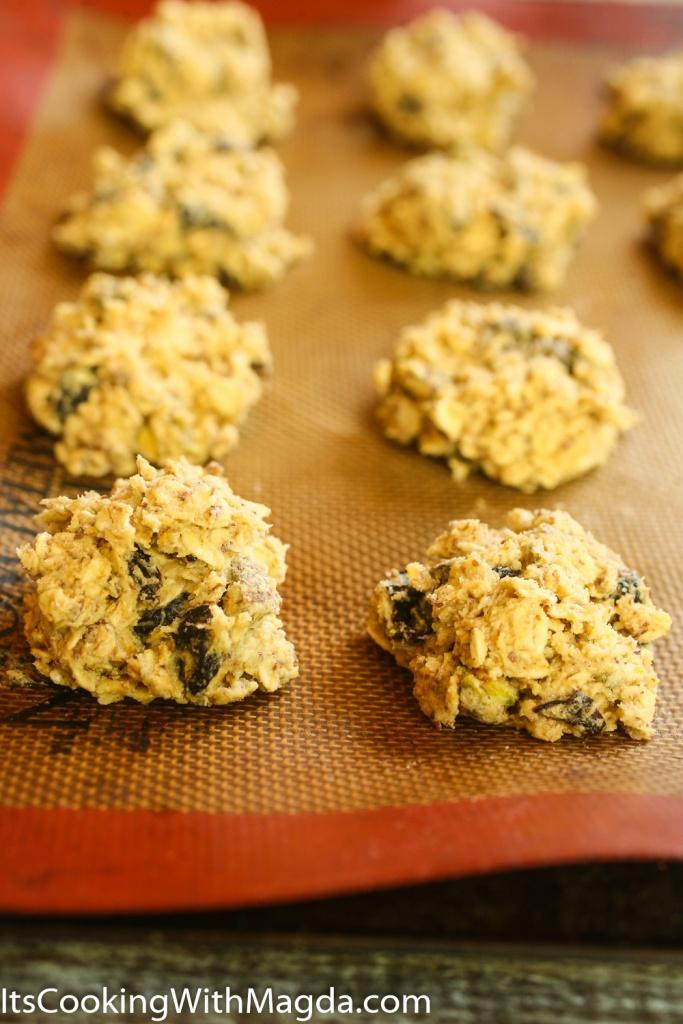 Pistachio cherry cookie dough balls on a baking pan