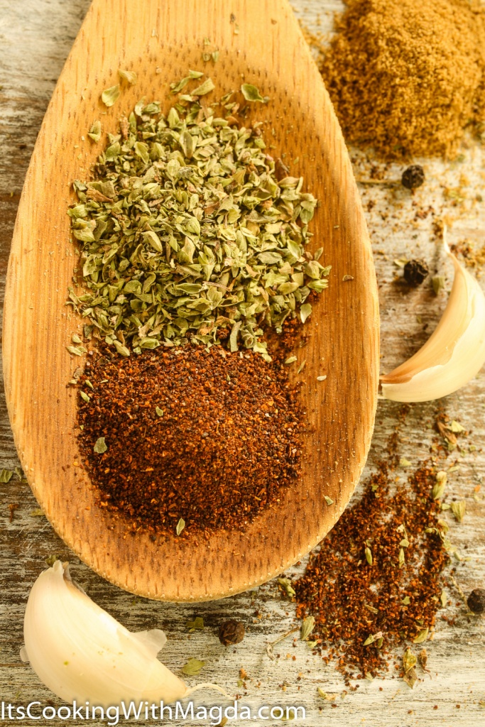 chili powder, dried oregano on a wooden spoon next to garlic