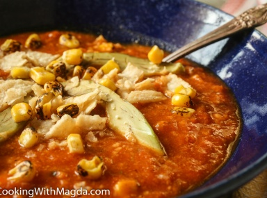 tortilla soup with roasted corn , avocado and chips on top