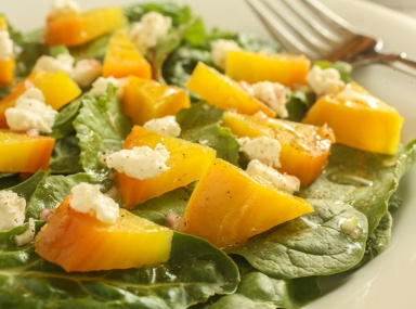 roasted golden beets on a bed of mixed greens with goat cheese