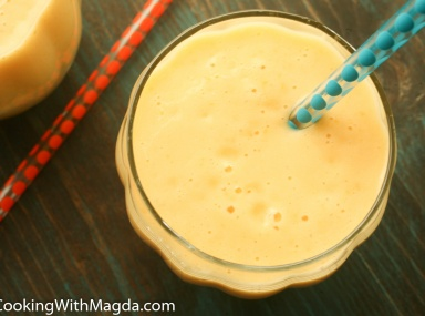 Tropical mango pineapple smoothie with a straw