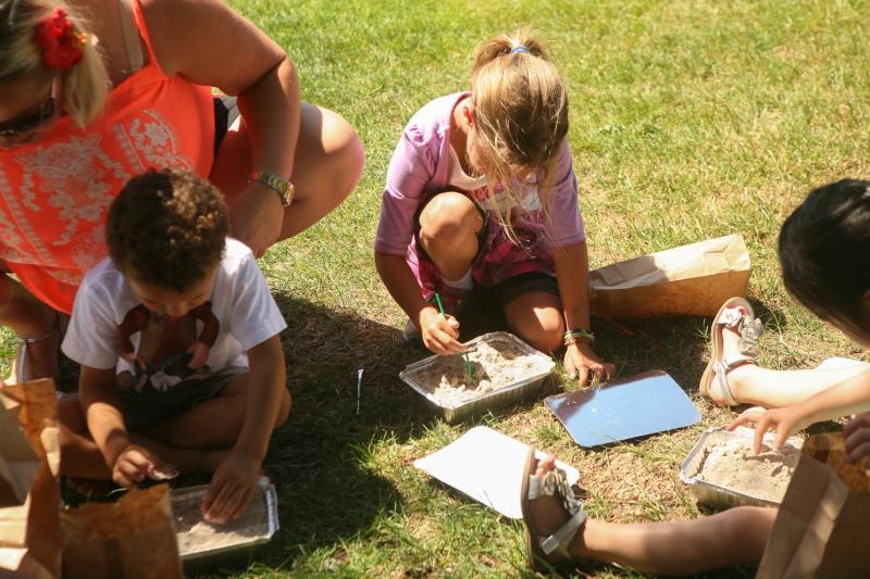 Kids looking for hidden dinosaur skeleton from a kit