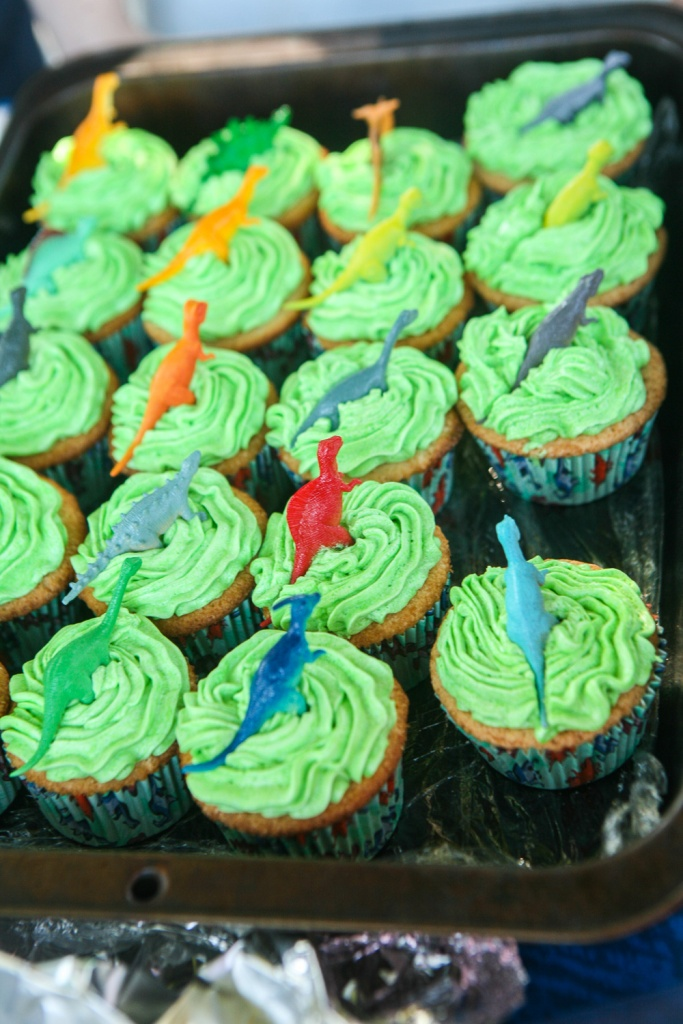Vanilla cupcakes with green vanilla frosting and a small dinosaur in the middle
