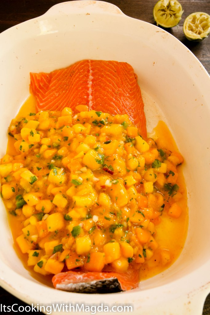 salmon fillet in a baking dish with mango salsa