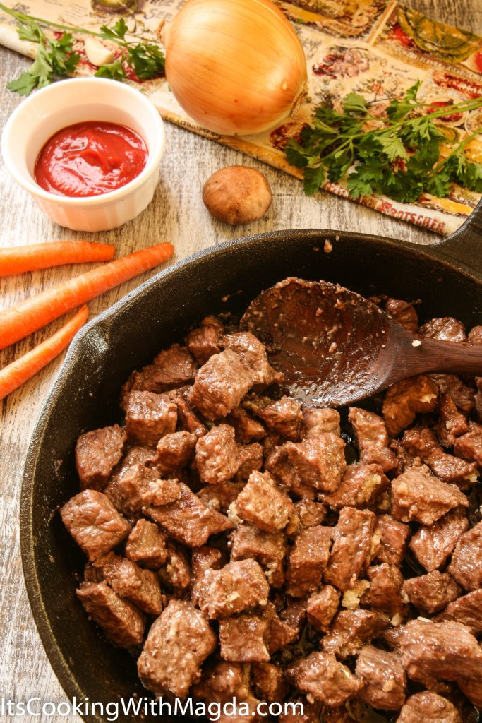 browned beef cubes with garlic on a skillet
