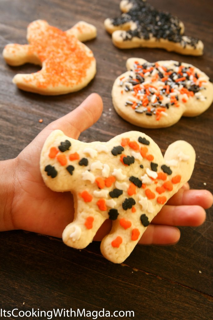 child's hand holding a Halloween cookie