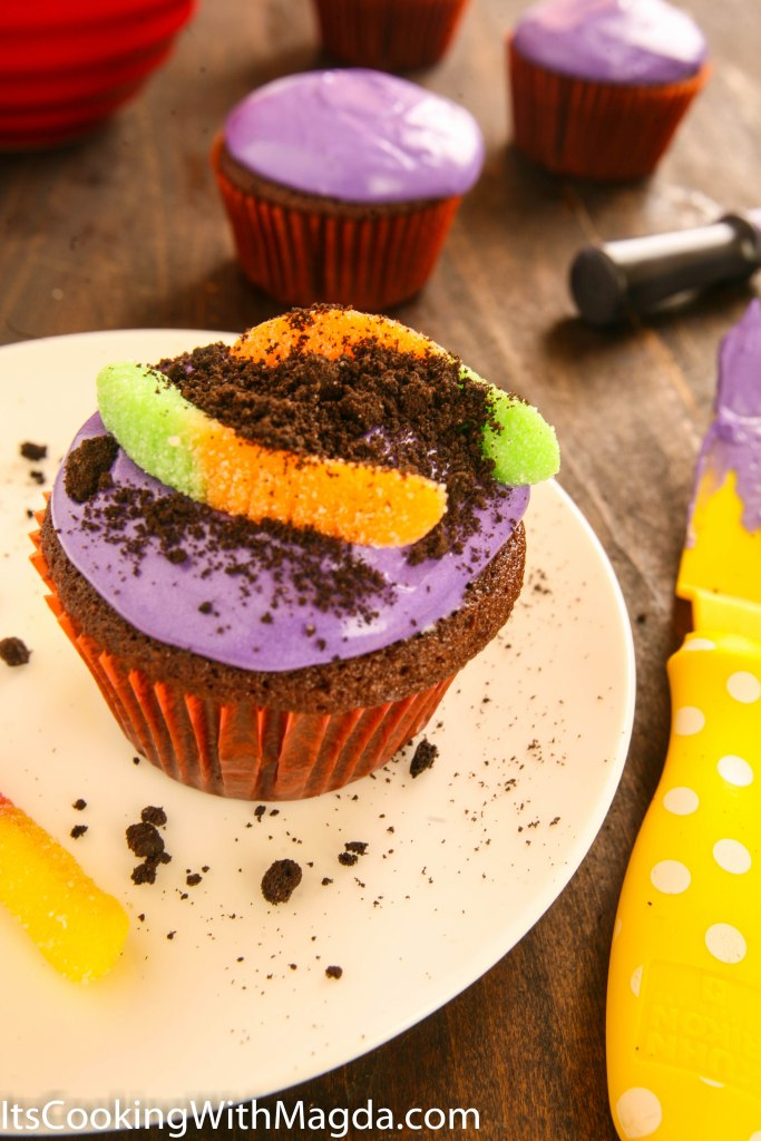 "Chocolate cupcake decorated with gummy worms and Oreo ""dirt"""