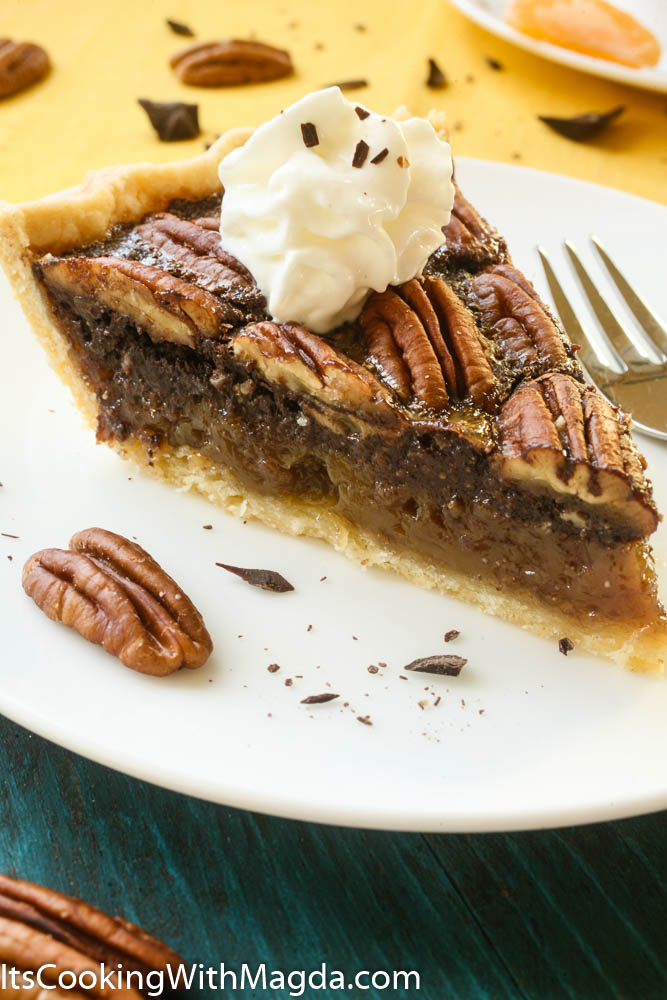 A slice of Chocolate Pecan Pie decorated with whipped cream