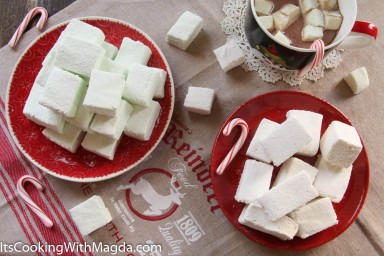 vanilla and peppermint marshmallows on red plates decorated with candy canes