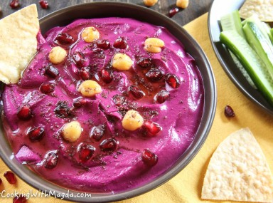 a bowl of beet hummus decorated with chickpeas, pomegranate seeds and sumac