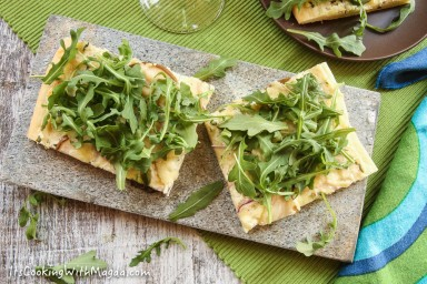 baked white pizza with ricotta cheese, pear, red onion and arugula