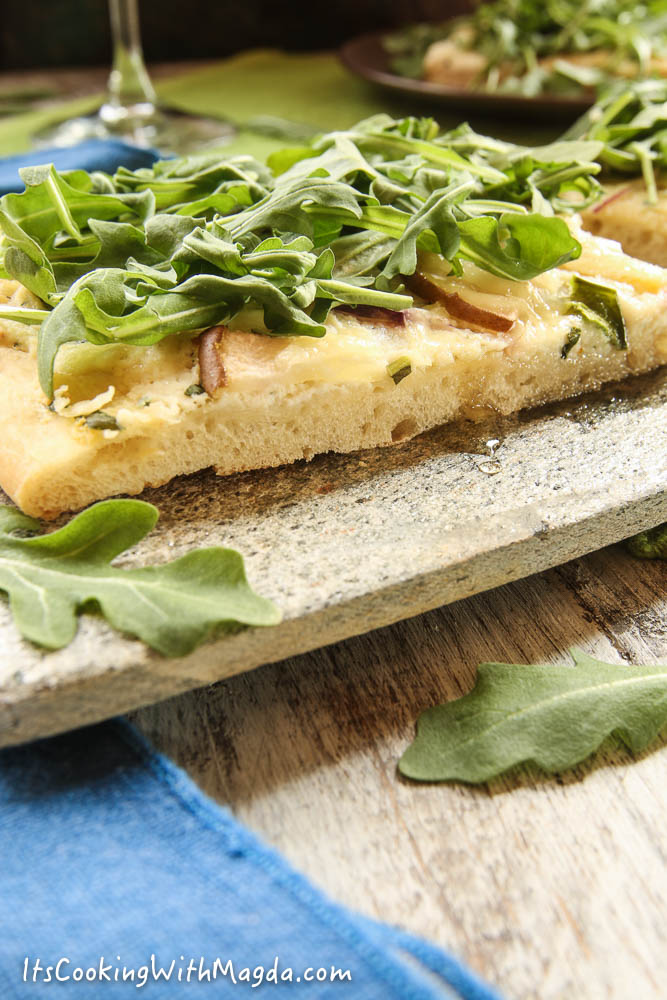 a piece of white pizza with ricotta cheese, pear and red onion topped with arugula