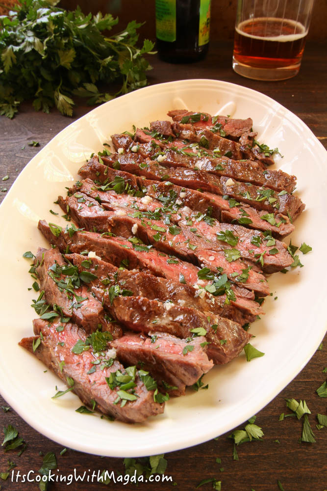 sliced skirt steak with garlic butter and chopped parsley