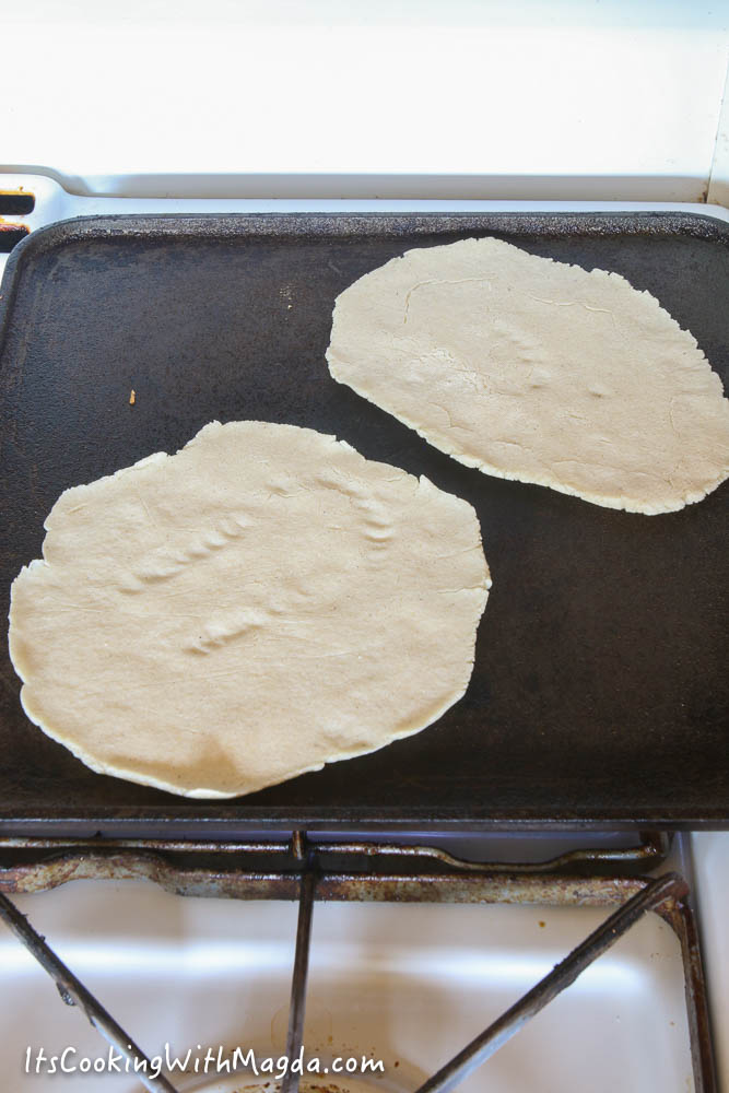 cooking corn tortillas on a hot griddle